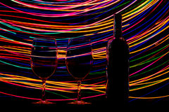 Vidros e garrafa de vinho no fundo e em fugas pretos Fotos de Stock Royalty Free