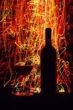 Vidros e garrafa de vinho no fundo preto Imagem de Stock