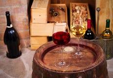 Vidros e garrafas do vinho vermelho e branco no tambor velho na adega de vinho Imagem de Stock Royalty Free