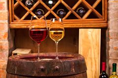 Vidros e garrafas do vinho vermelho e branco no tambor velho na adega de vinho Fotografia de Stock