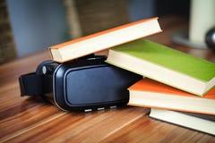 Vidros e livros de VR em uma tabela que simboliza a aprendizagem digital imagens de stock