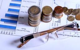 Vidros e moedas em gráficos financeiros Imagem de Stock Royalty Free