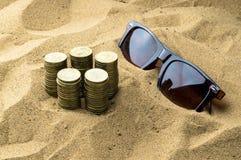 Vidros e moedas na areia Foto de Stock Royalty Free