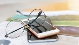 Vidros e telefone esperto em um livro na cafetaria fotos de stock royalty free