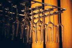 Vidros em seguido acima da cremalheira da barra no restaurante Fotografia de Stock
