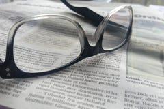 Vidros em um jornal Fotos de Stock