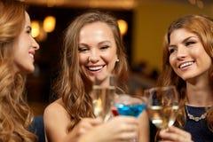 Vidros felizes do tinido das mulheres no clube noturno imagens de stock royalty free