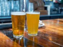 Vidros gelados completos da pinta da cerveja inglesa e das cervejas douradas que sentam-se no coun fotos de stock