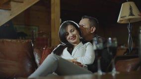 Vidros latin bonitos do tim-tim dos pares com vinho tinto na data no equipamento ocasional em casa Pares que têm momentos românti video estoque