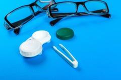 vidros, lentes de contato em uns recipientes e pinça no fundo azul Fotos de Stock Royalty Free