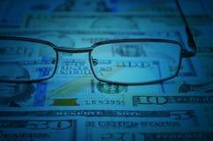 Vidros no dinheiro do dólar, conceito financeiro imagens de stock royalty free