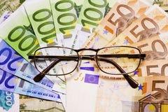 Vidros no fundo do dinheiro Fotos de Stock Royalty Free