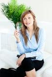 Vidros pensativos da terra arrendada da mulher de negócios em um sofá Foto de Stock