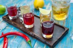 Vidros pequenos com bebidas coloridas em uma placa de madeira Imagens de Stock Royalty Free
