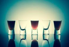 Vidros pequenos com os tiros de uma bebida do álcool que stainding em uma tabela Fotografia de Stock Royalty Free