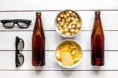 Vidros, petiscos, cerveja para o filme do whatchig na opinião superior do fundo de madeira branco Fotos de Stock