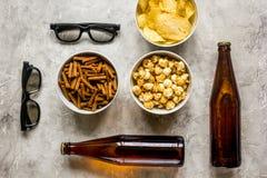Vidros, petiscos, cerveja para o filme do whatchig na opinião superior do fundo de pedra Imagens de Stock