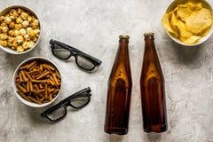 Vidros, petiscos, cerveja para o filme do whatchig na opinião superior do fundo de pedra Fotos de Stock