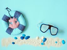 Vidros subaqu?ticos, corda de salvamento, escudos do mar e areia branca no fundo azul fotos de stock royalty free