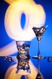 Vidros um gelo do uísque de Martini do cocktail, contra o fundo vermelho de efeitos da luz bonitos Fotos de Stock Royalty Free