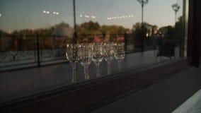 Vidros vazios do champanhe fora da janela do restaurante na noite filme