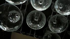 Vidros vazios para o vinho e o champanhe que penduram sobre uma cremalheira da barra vídeos de arquivo