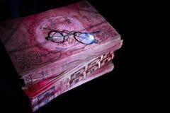 Vidros velhos mesmos dos olhos dos espetáculos do close up no livro vermelho muito velho que encontra-se no espelho para a reflex imagem de stock