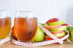 Vidros verdes e vermelhos frescos da fatia e do suco da maçã com fita de medição Imagem de Stock