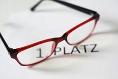 Vidros vermelhos acima do texto alemão 1 Platz, de que significa o primeiro lugar, conceito do júri da competição imagem de stock royalty free