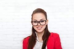 Vidros vermelhos de sorriso do revestimento do desgaste da cara da mulher de negócios Imagem de Stock