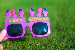 Vidros vermelhos do feliz aniversario na grama Foto de Stock Royalty Free
