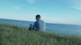 Vidros vestindo à moda de um homem novo e vestir uma camiseta azul, escutando a música em fones de ouvido em um smartphone e filme