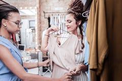 Vidros vestindo úteis do assistente de compra que ajudam seu cliente constante fotos de stock