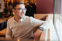Vidros vestindo alegres do homem novo que sentam-se no café Imagem de Stock Royalty Free