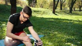 Vidros vestindo atrativos do homem novo que esticam seus pés adiantados na manhã em Green Park bonito outdoor Na filme