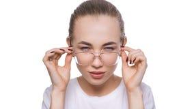 Vidros vestindo da jovem mulher que olham a c?mera com problema com olhos, conceito da d?vida e da desconfian?a dos cuidados m?di fotos de stock