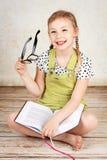 Vidros vestindo da menina esperta e leitura de um livro Imagem de Stock