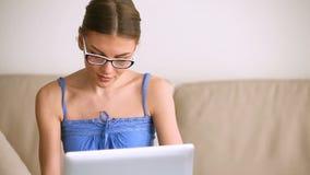 Vidros vestindo da moça bonita usando o portátil, sorrindo para a câmera video estoque
