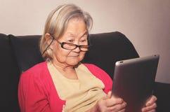 Vidros vestindo da mulher adulta em casa que leem algo tabuleta Imagem de Stock