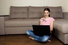 Vidros vestindo da mulher bonita que surfam e que registram no Internet usando seu computador Observação nova e bonita da menina  imagens de stock royalty free
