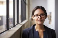 Vidros vestindo da mulher de negócios nova da raça misturada, retrato imagem de stock