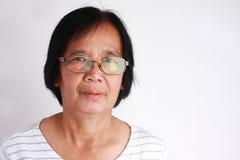 Vidros vestindo da mulher idosa asiática no fundo branco imagens de stock