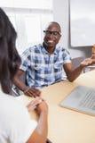 Vidros vestindo de sorriso do homem de negócios durante uma reunião Fotos de Stock