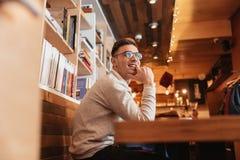 Vidros vestindo de sorriso do homem que sentam-se no café Fotos de Stock Royalty Free