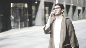 Vidros vestindo de um indivíduo do moderno e um revestimento caqui que fala em seu smartphone na rua Tiro do retrato Fotos de Stock