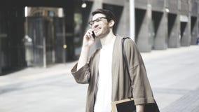 Vidros vestindo de um indivíduo do moderno que falam em seu smartphone na rua Tiro do retrato Fotos de Stock