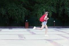 Vidros vestindo de uma menina running, short da sarja de Nimes, camisa cinzenta com trouxa Fotografia de Stock