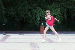 Vidros vestindo de uma menina running, short da sarja de Nimes, camisa cinzenta com trouxa Imagem de Stock Royalty Free