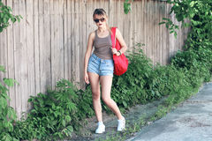 Vidros vestindo de uma menina, short da sarja de Nimes, camisa cinzenta com trouxa Fotografia de Stock