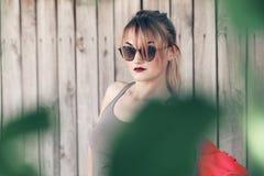 Vidros vestindo de uma menina, short da sarja de Nimes, camisa cinzenta com trouxa Fotos de Stock